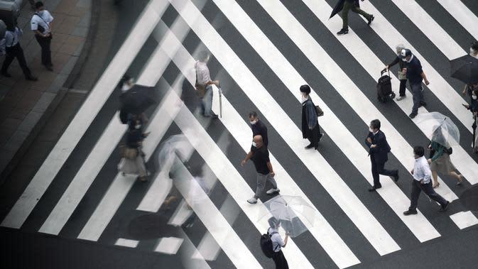 Orang-orang memakai masker untuk membantu mencegah penyebaran virus corona berjalan di penyeberangan pejalan kaki di Tokyo, (23/9/2020). Badai tropis di Samudra Pasifik perlahan mendekati wilayah Tokyo pada hari Rabu. (AP Photo/Eugene Hoshiko)