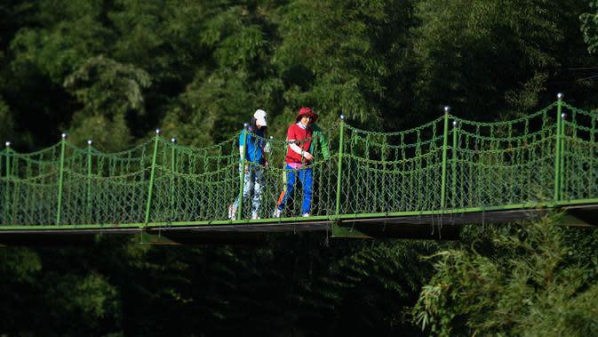 Wisatawan berjalan di sebuah jembatan gantung di Desa Luci, Kota Fuchunjiang, Tonglu, China, 6 September 2020. Pengunjung dapat mencicipi kehidupan pedesaan yang tenang tanpa hiruk pikuk di Kota Fuchunjiang dengan desa-desa berpemandangan indah dan objek wisata populer. (Xinhua/Huang Zongzhi)