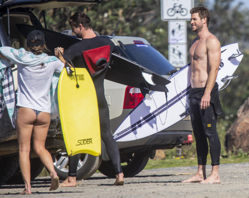 Liam Hemsworth Chris Hemsworth put surfboards into their car