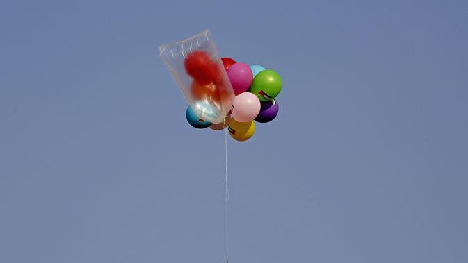 Balon dengan alat peledak terbang ke arah Israel di dekat kamp pengungsi al-Bureij, sepanjang perbatasan Israel- Jalur Gaza (12/8/2020). (AFP Photo/Mohammed Abed)