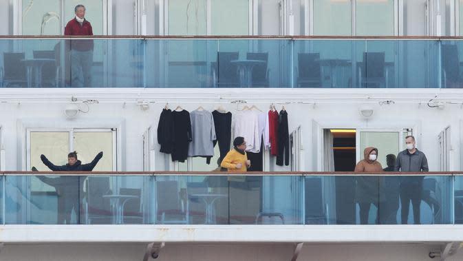 Penumpang beraktivitas saat dikarantina di balkon kapal pesiar Diamond Princess di Daikoku Pier Cruise Terminal di Yokohama (7/2/2020). Kementerian Kesehatan Jepang mengonfirmasi 41 penumpang kapal pesiar itu positif terinfeksi virus Corona. (AFP/Jiji Press)