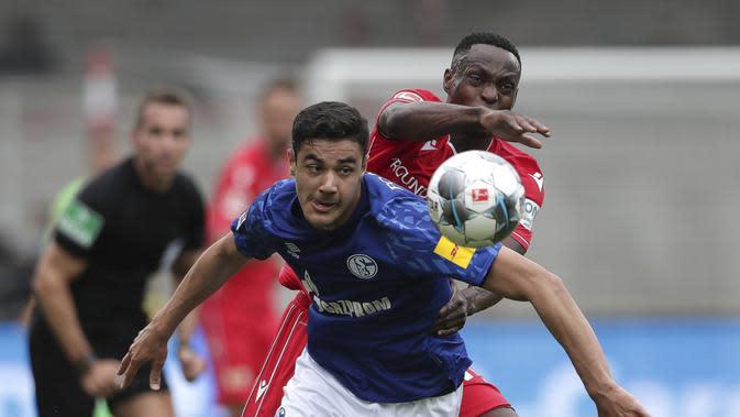 Pemain Union Berlin, Anthony Ujah, berebut bola dengan pemain Schalke, Ozan Kabak, pada laga Bundesliga di Weserstadion Minggu (7/6/2020). Kedua tim bermain imbang 1-1. (AP/Michael Sohn)