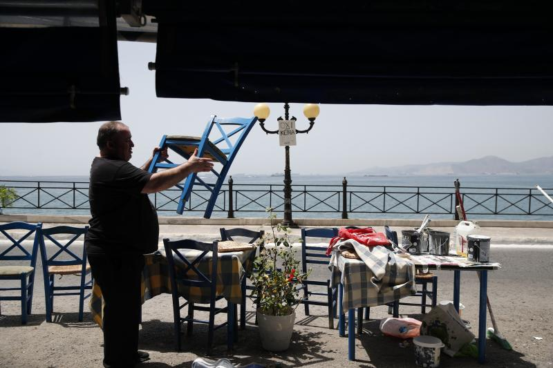 A worker places chairs at a fish restaurant ahead of its reopening in Piraeus, near Athens, Wednesday, May 20, 2020.Next Monday, bars, cafes and restaurants will be allowed to serve clients on the premises, with patrons limited to 6 per table, except for families with children. Greece is gradually lifting quarantine restrictions after the lockdown against the coronavirus outbreak. (AP Photo/Thanassis Stavrakis)