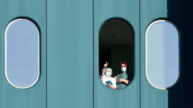 Petugas medis menunjukkan isyarat kemenangan dari jendela Rumah Sakit Dubrava, Kroasia, 15 Maret 2020. Pandemi virus corona COVID-19 membuat Kroasia menangguhkan semua layanan transportasi umum selama 30 hari ke depan. (Photo by Denis LOVROVIC/AFP)
