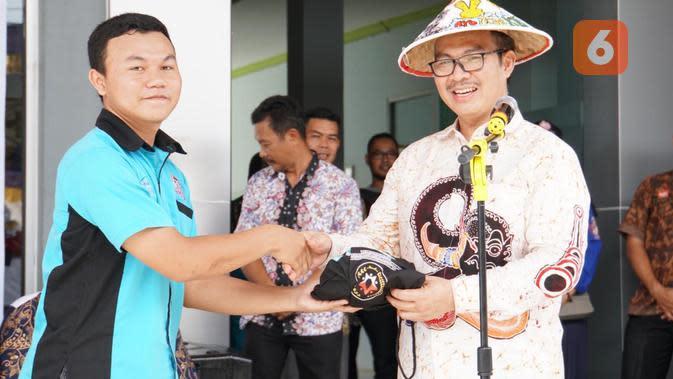 Kepala BKKBN, Hasto Wardoyo, menyerahkan sebuah kenang-kenangan untuk salah seorang remaja putra yang berhasil menjawab pertanyaan mengenai bahayanya menikah dini (Foto: Humas BKKBN)