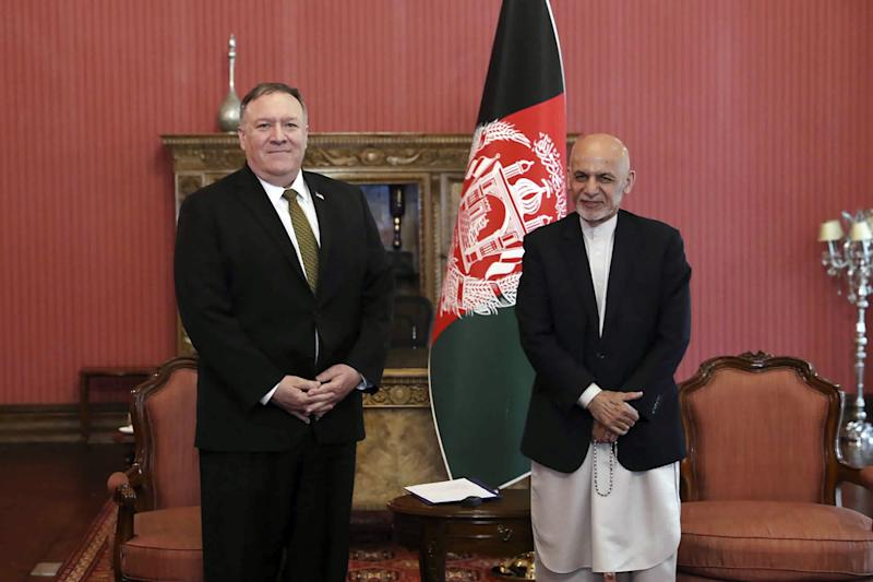 U.S. Secretary of State Mike Pompeo, left, stands with Afghan President Ashraf Ghani, at the Presidential Palace in Kabul, Afghanistan, Monday, March 23, 2020. Pompeo was in Kabul on an urgent visit Monday to try to move forward a U.S. peace deal signed last month with the Taliban, a trip that comes despite the coronavirus pandemic, at a time when world leaders and statesmen are curtailing official travel. (Afghan Presidential Palace via AP)