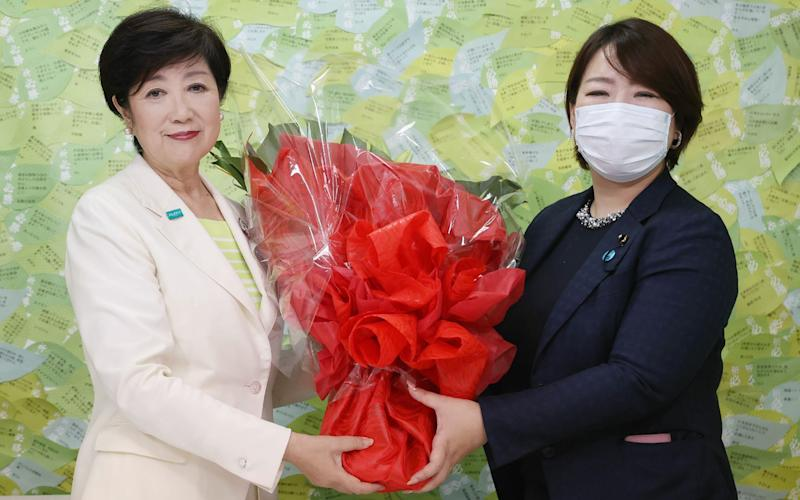 Tokyo governor Yuriko Koike receives a bouquet of flowers after her election win - AFP