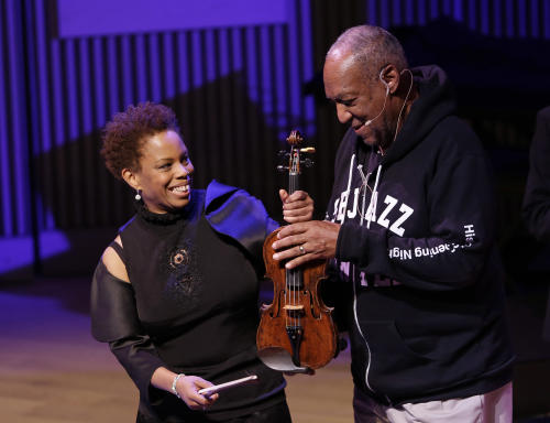 Bill Cosby, right, jokes with Regina Carter about her violin during the opening night concert of the SFJAZZ Center Wednesday, Jan. 23, 2013 in San Francisco. The 700-seat, specially designed concert hall nestled in the heart of the city's arts district attracted a crowd of hundreds with a high-energy, inaugural celebration emceed by Bill Cosby. Billed as the first freestanding building in the West built for jazz performance and education, the center opened Wednesday after raising more than $60 million over more than a decade to build a home for SFJAZZ, the nonprofit that puts on the city's jazz festival. (AP Photo/Eric Risberg)