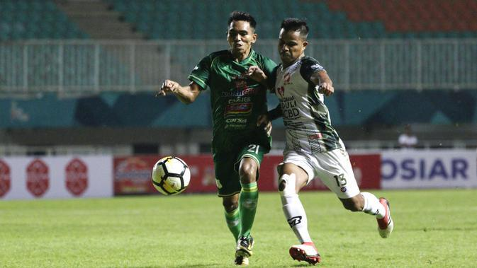 Gelandang PSMS Medan, Frets Butuan, berebut bola dengan gelandang PS Tira, Manahati Lestusen, pada laga Liga 1 di Stadion Pakansari, Jawa Barat, Rabu (5/12). PSMS kalah 2-4 dari PS Tira. (Bola.com/Yoppy Renato)