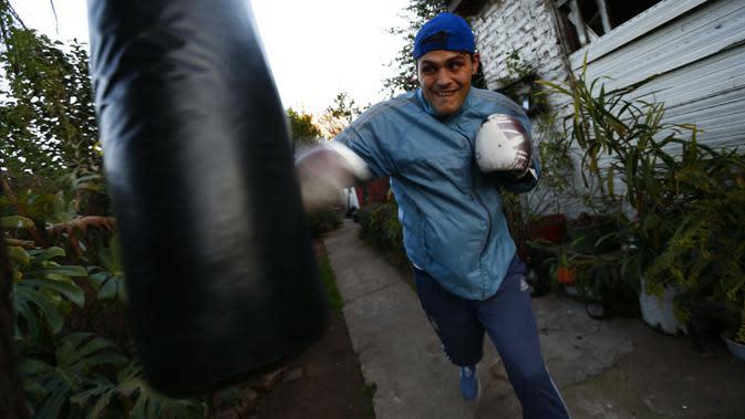 Yamil Peralta melakukan latihan di rumahnya di Jose C. Paz di pinggiran Buenos Aires, Argentina, 29 Juli 2020. Di tengah lockdown, petinju profesional ini membuat alat olahraga darurat di rumahnya untuk berlatih dengan harapan lolos kualifikasi untuk Olimpiade Tokyo 2021. (AP Photo/Marcos Brindicci)