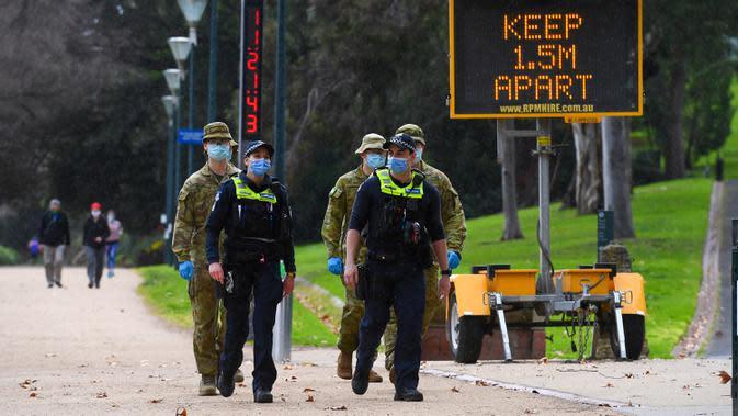 Petugas kepolisian dan tentara berpatroli di jalur lari yang populer di Melbourne, Selasa (4/8/2020). Negara bagian Victoria di Australia, khususnya ibu kota Melbourne mengumumkan status darurat bencana COVID-19 pada Minggu (2/8) waktu setempat. (William WEST / AFP)