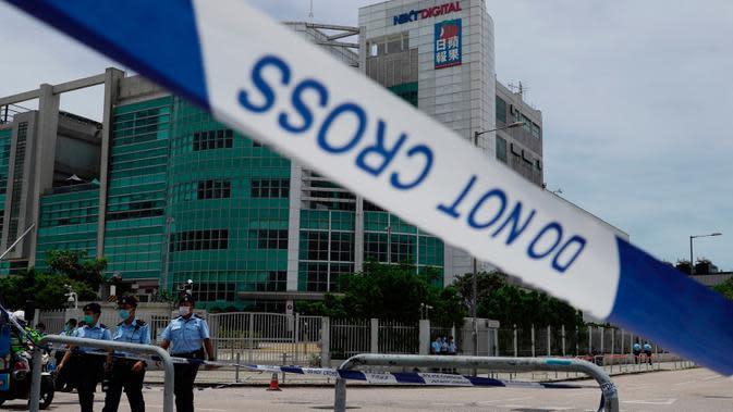 Petugas kepolisian berjaga di luar gedung Apple Daily saat taipan media Hong Kong, Jimmy Lai ditangkap di rumahnya di Hong Kong, Senin (10/8/2020). Lai ditangkap atas tuduhan pelanggaran Undang-Undang Keamanan Nasional Hong Kong karena dianggap berkolusi dengan kekuatan asing. (AP Photo/Vincent Yu)