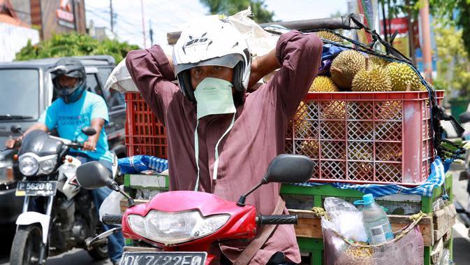 Pedagang durian mengenakan masker yang diberikan anggota gugus tugas Covid-19 Banyuwangi.