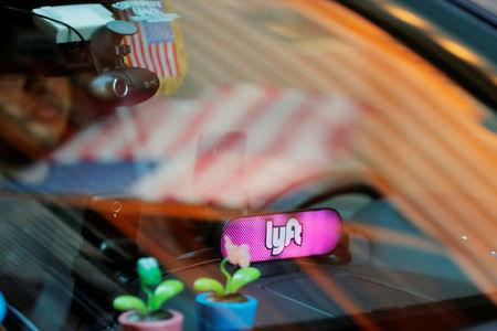 FILE PHOTO: A car with a Lyft logo in its window drives down a street as the company prepares for its upcoming IPO in New York, U.S., March 19, 2019. REUTERS/Lucas Jackson/File Photo