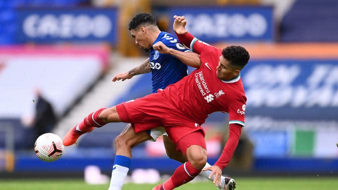 Gelandang Liverpool, Roberto Firmino berebut bola dengan gelandang Everton, Allan (Laurence Griffiths / POOL / AFP)