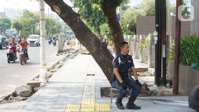 Petugas kemanan duduk dekat pohon yang berada di jalur pedestrian Jalan Kramat Raya, Jakarta, Jumat (8/11/2019). Sepanjang pengerjaan jalur pedestrian, pohon yang berada di jalur tersebut rencananya juga akan direvitalisasi dan diremajakan. (Liputan6.com/Immanuel Antonius)