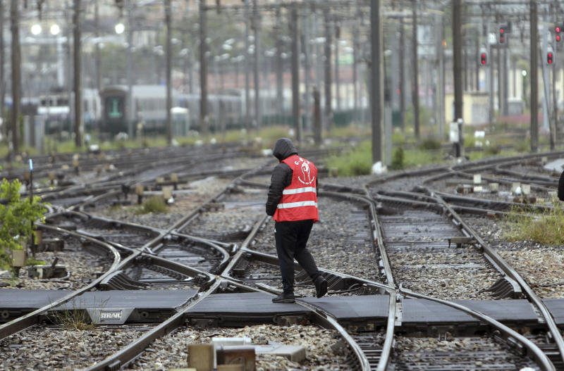 FILE - In this May 14, 2018 file photo, a striking rail worker walks on the tracks of the Saint-Charles train station, in Marseille, southern France. France's rail operator SNCF and the Paris Metro say nationwide strikes will wipe out most services Thursday, impacting millions. The SNCF expects that 9 out of 10 high-speed trains won't run and that half of the Eurostar services linking France and Britain will be canceled, too. (AP Photo/Claude Paris, File)