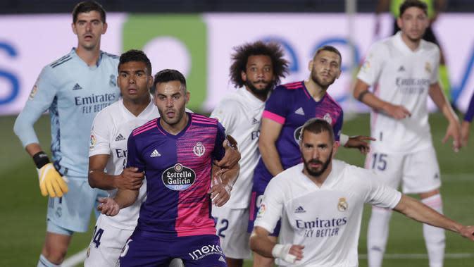 Penyerang Real Madrid, Karim Benzema, berebut bola dengan pemain Real Valladolid pada laga lanjutan Liga Spanyol di Estadio Alfredo Di Stefano, Kamis (1/10/2020) dini hari WIB. Real Madrid menang 1-0 atas Valladolid. (AP Photo/Manu Fernandez)