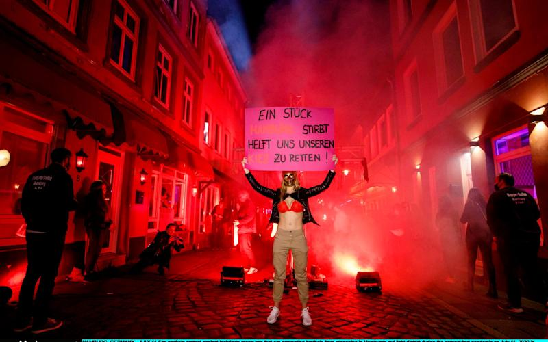 HAMBURG, GERMANY - JULY 11: Sex workers protest against lockdown measures that are preventing brothels from reopening in Hamburg's red light district during the coronavirus pandemic on July 11, 2020 in Hamburg, Germany. Sex workers across Germany are demanding an easing of ongoing lockdown measures that are preventing them from resuming their work. While authorities have lifted lockdown measures for most businesses in Germany, some, especially for those that involve close physical contact, remain in place. Legal sex workers say they are being treated unfairly, claiming they have developed adequate hygienic measures to prevent the spread of the virus and point out that other businesses that require similar physical proximity, such as hair salons and tattoo parlours, have been allowed to reopen. (Photo by Morris MacMatzen/Getty Images) - Morris MacMatzen/Getty Images Europe