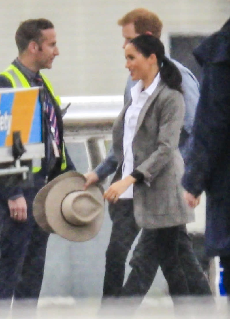 Meghan holding onto her Akubra hat at the airport on the way to Dubbo. Photo: Media Mode, meghan markle prince harry dubbo, meghan markle prince harry australia, meghan markle serena williams jacket, meghan markle pregnant, meghan markle akubra