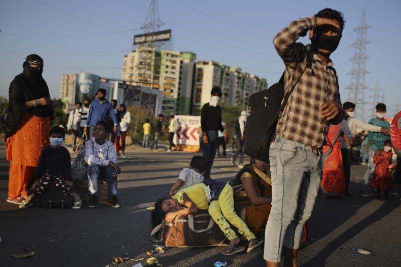 In this Saturday, March 28, 2020, file photo, a young girl lies on a luggage as she along with her family awaits transportation to her village following a lockdown amid concern over spread of coronavirus in New Delhi, India. Over the past week, India's migrant workers - the mainstay of the country's labor force - spilled out of big cities that have been shuttered due to the coronavirus and returned to their villages, sparking fears that the virus could spread to the countryside. It was an exodus unlike anything seen in India since the 1947 Partition, when British colothe subcontinent, with the 21-day lockdown leaving millions of migrants with no choice but to return to their home villages. (AP Photo/Altaf Qadri)