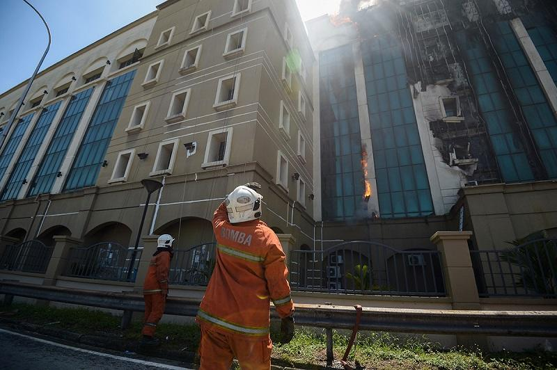 Fire and Rescue department personnel attempt to put out the fire at the EPF building at Jalan Gasing in Petaling Jaya February 13, 2018. — Picture by Mukhriz Hazim