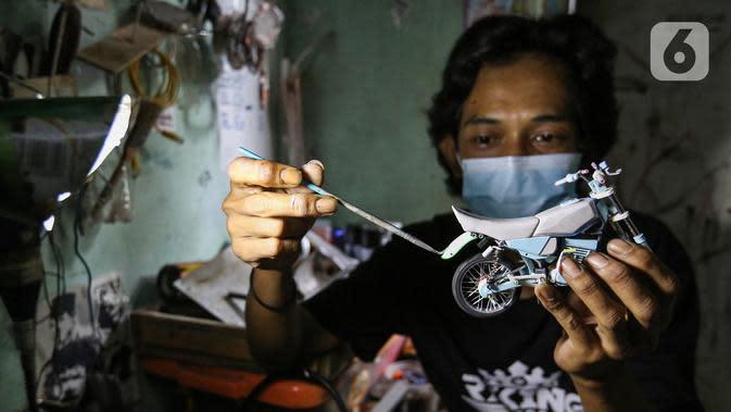 Pengrajin Wawang Kurniawan, mengecat miniatur motor RX-King di Kampung Dukuh, Serua, Tangerang Selatan, Sabtu (17/10/2020). Miniatur motor yang terbuat dari barang bekas paralon, kaleng minuman mulai digeluti sejak tahun 2018. (Liputan6.com/Fery Pradolo)