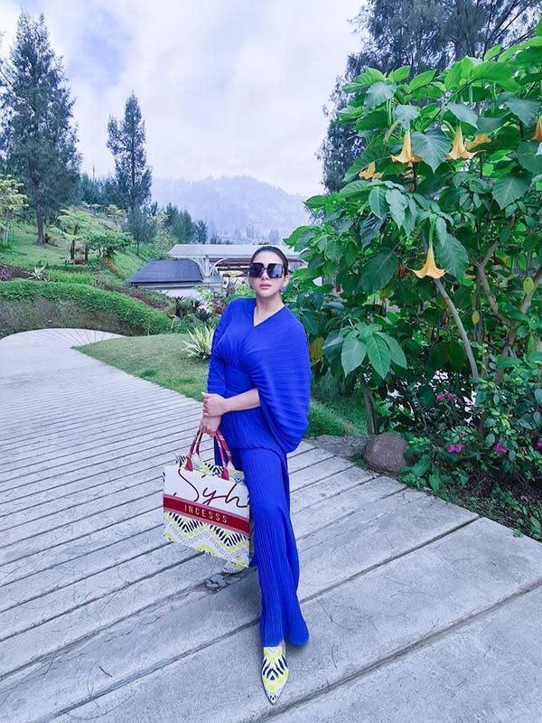 Selanjutnya, gaya Syahrini di tengah liburannya. Ia mengenakan busana berwarna biru dan tak ketinggalan kacamatanya yang super kece. Tak heran memang melihat gaya Syahrini yang selalu menarik. (Instagram/princessyahrini)
