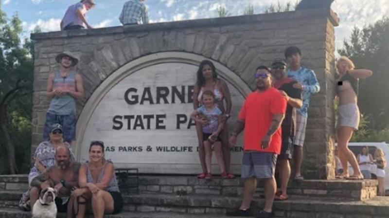 The Texas family posing for a photo as a random woman exposes her breast while photobombing.