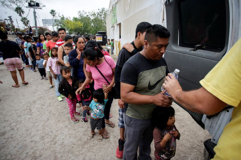 Migrants queue for water at an encampment of more than 2,000 migrants seeking asylum in the U.S., as local authorities prepare to respond to the coronavirus disease (COVID-19) outbreak, in Matamoros