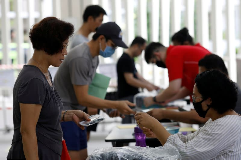 Residents receive free reusable masks distributed by the government at a community center, as stricter measures are announced to combat the outbreak of the coronavirus disease (COVID-19) in Singapore