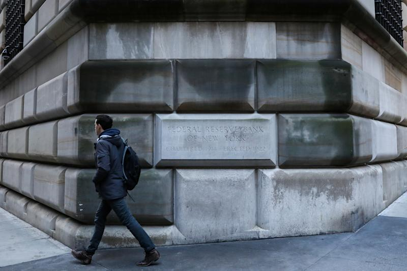 A man passes by the corner stone on the Federal Reserve Bank of New York in the financial district in New York City, U.S., March 4, 2019. REUTERS/Brendan McDermid