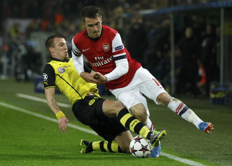Borussia Dortmund's Grosskreutz tackles Arsenal's Ramsey during Champions League soccer match in Dortmund