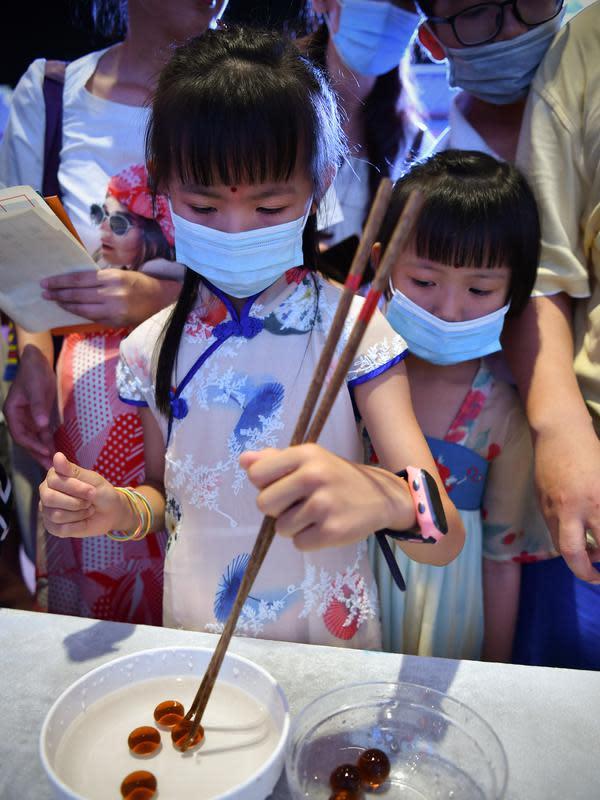 Seorang anak mencoba mengambil kelereng dengan sumpit dalam acara perayaan Festival Pertengahan Musim Gugur di Museum Hainan, Haikou, ibu kota Provinsi Hainan, China selatan (1/10/2020). (Xinhua/Guo Cheng)