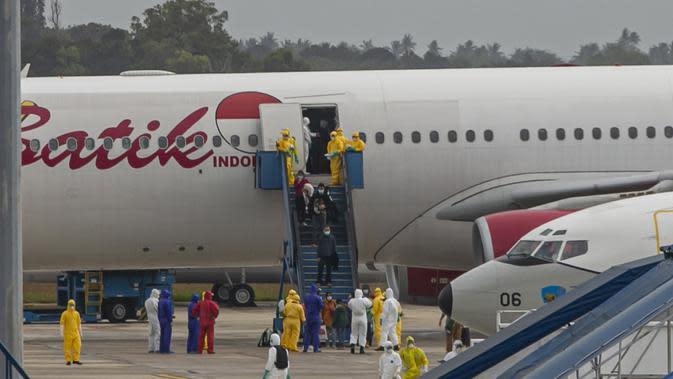 Sejumlah Warga Negara Indonesia (WNI) yang dievakuasi dari Wuhan, China keluar dari pesawat Batik Air di bandara internasional Hang Nadim, Batam, Minggu (2/2/2020). Sebanyak 245 WNI di Wuhan dievakuasi ke Indonesia terkait merebaknya virus corona di kota tersebut. (AP Photo/Luth Panjalu)