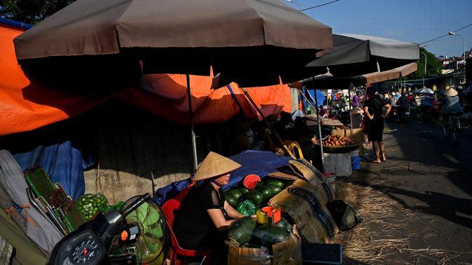 Penjual yang menjual semangka menunggu pelanggan di pasar grosir di Hanoi (26/8/2020). (AFP Photo/Manan Vatsyayana)