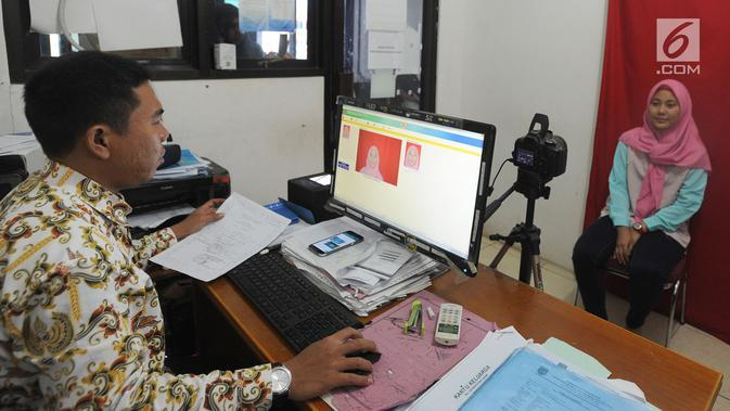 Petugas melakukan proses perekaman data pembuatan e-KTP di Kantor kelurahan Cinere, Depok, Kamis (27/12). Hari ini Disdukcapil daerah melaksanakan pelayanan jemput bola perekaman E-KTP serentak khusus pemula secara nasional. (Merdeka.com/Arie Basuki)