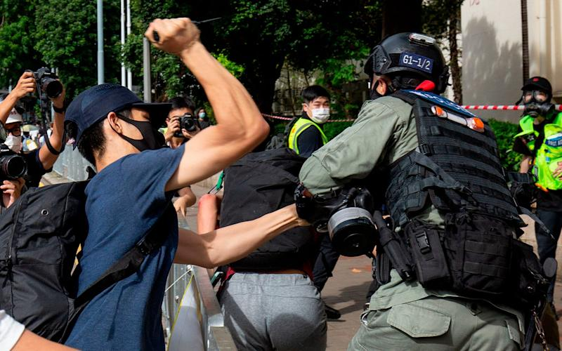 A protester (L) using a sharp object against a police officer (R) who is trying to detain a man (C) during a rally against a new national security law - ALASTAIR PIKE/AFP