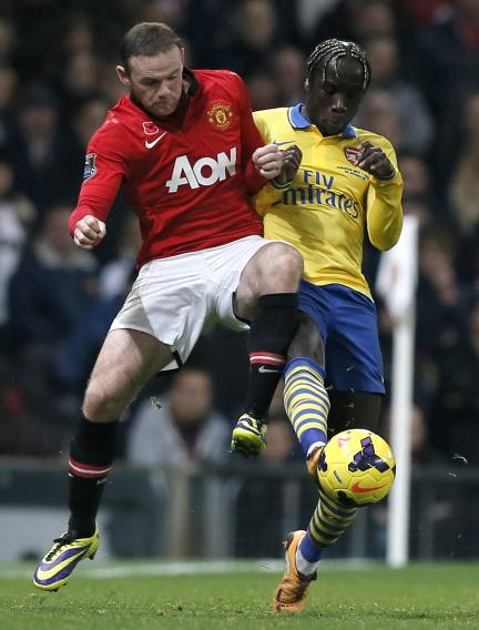 Manchester United's Rooney challenges Arsenal's Sagna during their English Premier League soccer match in Manchester