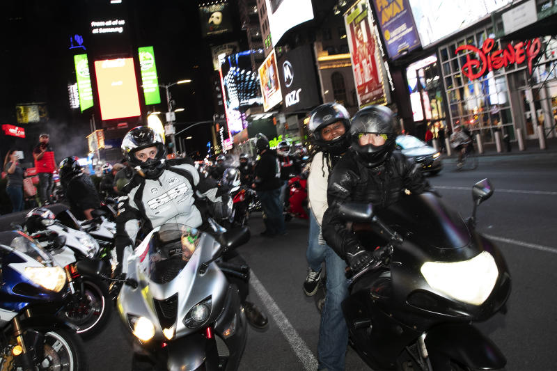 In this Saturday, May 2, 2020 photo, a crew of motorcyclists stops for photos in New York's Times Square during the coronavirus pandemic. (AP Photo/Mark Lennihan)