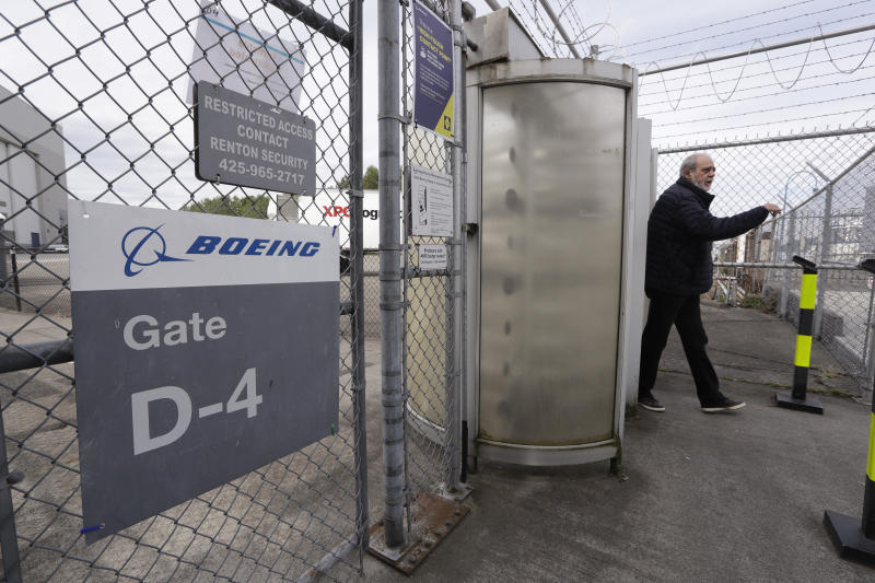 A Boeing worker walks out of a gate for a smoke break at an airplane manufacturing plant Wednesday, April 29, 2020, in Renton, Wash. Boeing says it will cut about 10% of its work force and slow production of planes as it deals with the ongoing grounding of its best-selling plane and the coronavirus pandemic. With air travel falling sharply because of the virus, airlines have delayed orders and deliveries of new planes, reducing Boeing's revenue. (AP Photo/Elaine Thompson)