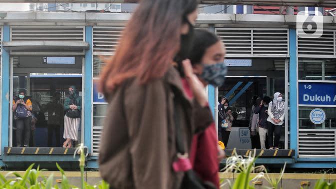 Pegawai pulang kerja menunggu bus Trassnjakarta di Halte Dukuh Atas, Jalan Sudirman, Jakarta, Selasa (12/5/2020). Pemerintah memberi kelonggaran bergerak bagi warga berusia di bawah 45 tahun untuk mengurangi angka pemutusan hubungan kerja (PHK) akibat pandemi COVID-19. (Liputan6.com/Johan Tallo)