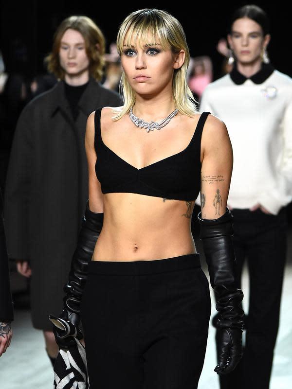 Miley Cyrus berjalan di catwalk untuk show Marc Jacobs Fall 2020 selama New York Fashion Week, Rabu (12/2/2020). Miley Cyrus memancarkan energi rockstar dalam balutan bralette hitam dipadu celana panjang dengan warna senada serta menenteng coat zebra. (JAMIE MCCARTHY/GETTY IMAGES /AFP)