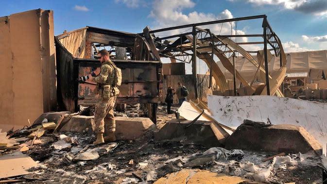 Tentara dan jurnalis AS memeriksa puing-puing di pangkalan udara Ain al-Asad, Anbar, Irak, Senin (13/1/2020). Iran menghujani pangkalan militer AS tersebut dengan rudal sebagai balasan atas kematian Jenderal Qasem Soleimani. (AP Photo/Qassim Abdul-Zahra)