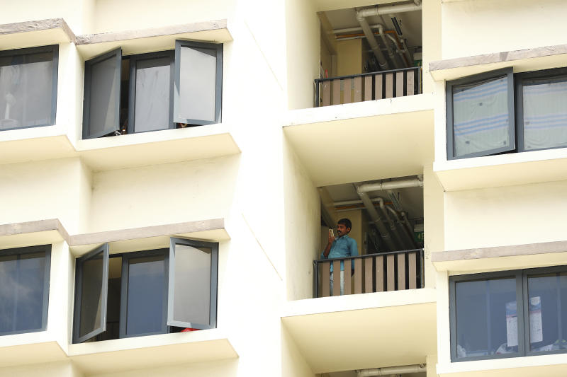 A foreign worker talks on the phone outside his room at the WestLite Toh Guan dormitory after it was declared an isolation area under the Infectious Diseases Act, following a spike in the number of COVID-19 cases in several foreign worker dormitories in Singapore, Friday, April 10, 2020. The tiny city-state of Singapore, with under six million people, has been hailed as a model in its swift response to the virus in the early days. But it overlooked the massive pool of migrant workers living in close quarters where social distancing is impossible and conditions are ripe for the virus spread. (AP Photo/Yong Teck Lim)