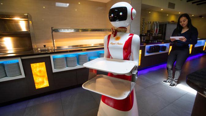 Leah Hu menunjukkan penggunaan robot pengganti pelayan sebagai bagian dari uji coba langkah-langkah aturan jaga jarak di restoran keluarga Royal Palace, Belanda, 27 Mei 2020. Robot ini bertugas menyapa pelanggan, menyajikan makanan dan minuman dan mengembalikan alat makan. (AP/Peter Dejong)