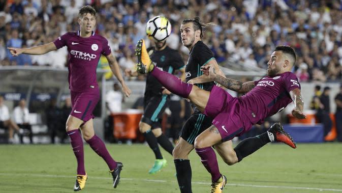 Bek Manchester City, Nicolas Otamendi, membuang bola dari jangkauan gelandang Real Madrid, Gareth Bale, pada laga ICC di Stadion Memorial Coliseum, California, Rabu (26/7/2017). Manchester City menang 4-1 atas Real Madrid. (AP/Jae C Hong)