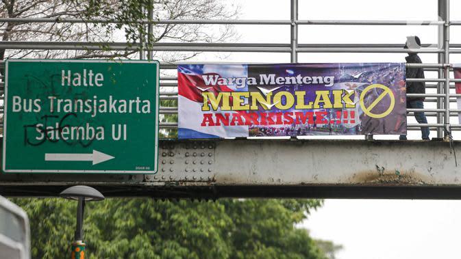 Spanduk imbauan tolak anarkisme terpasang di JPO di Jakarta, Minggu (11/10/2020). Spanduk imbauan untuk tidak melakukan aksi anarkisme merebak di sejumlah kawasan di Jakarta pascaaksi unjuk rasa massa yang menolak pengesahan Omnibus Law UU Cipta Kerja. (Liputan6.com/Faizal Fanani)