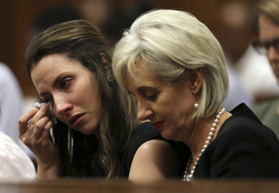 Sister Aimee Pistorius, left, cries alongside aunt Lois Pistorius as they attend the fourth day of sentencing proceedings for Oscar Pistorius in the high court in Pretoria, South Africa, Thursday, Oct. 16, 2014. A judge is listening to testimony from witnesses before deciding what punishment the double-amputee Olympian must serve after convicting him of culpable homicide for shooting Steenkamp in his home last year. (AP Photo/Siphiwe Sibeko, Pool)