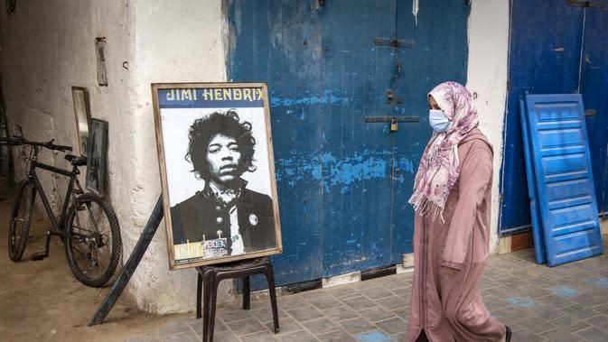 Warga melintas di depan poster Jimi Hendrix kota pesisir Maroko Essaouira pada 10 September 2020. Catatan sejarah mengungkap bahwa Hendrix wafat akibat tersedak muntahannya sendiri di sebuah hotel di London pada 18 September 1970 setelah menelan pil tidur dan minum anggur merah. (AFP/Fadel Senna)